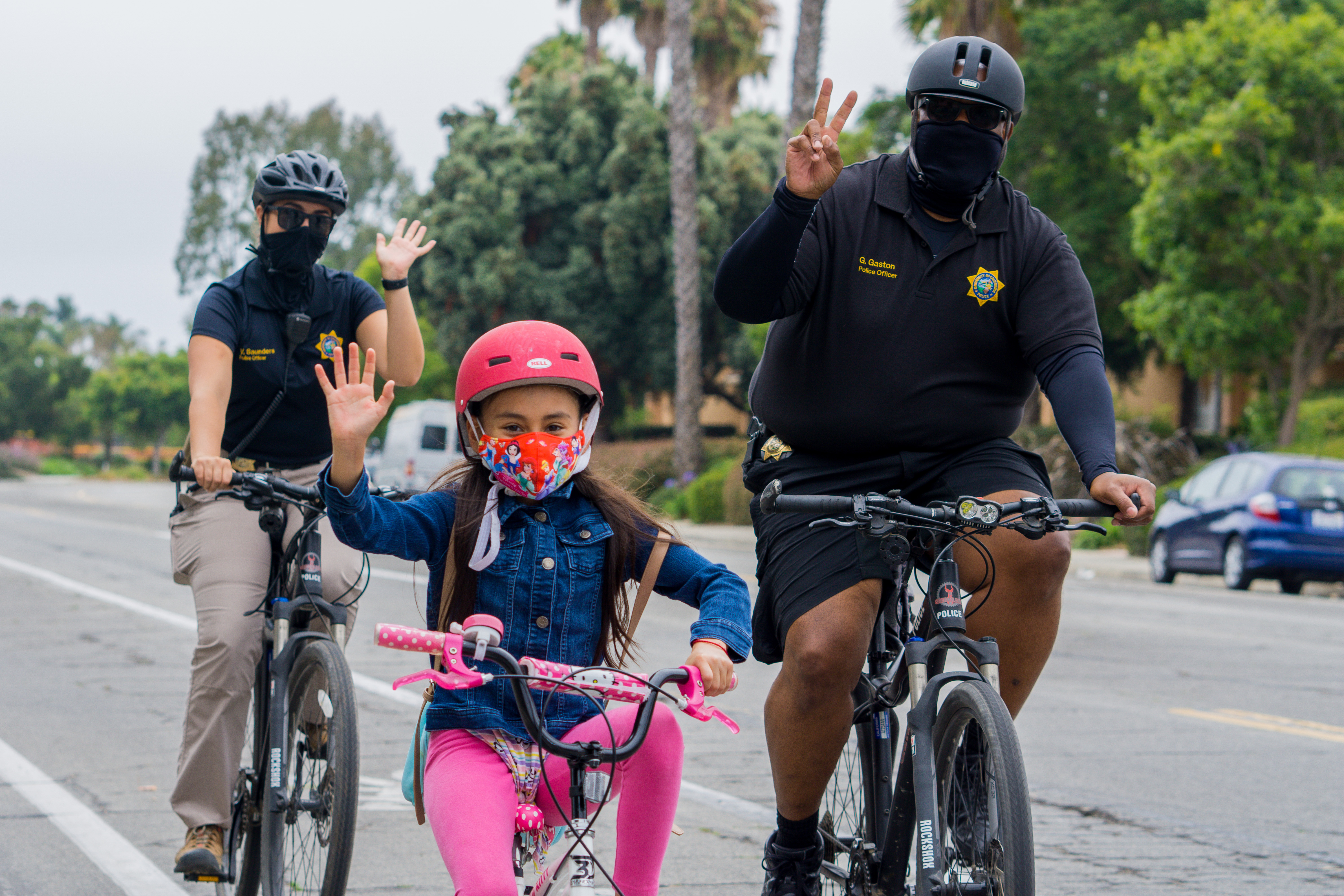 UCSB Police Officers on a socially distanced bike ride with a child